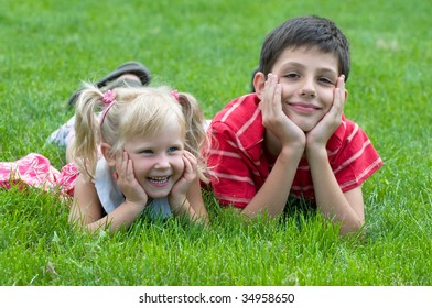 a little girl and a boy are lying on the grass in the park