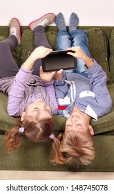 little girl and boy lying upside down on bed and play with tablet