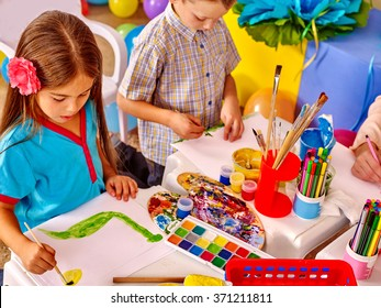 Little girl and boy  painting picture by brush on table in  kindergarten .