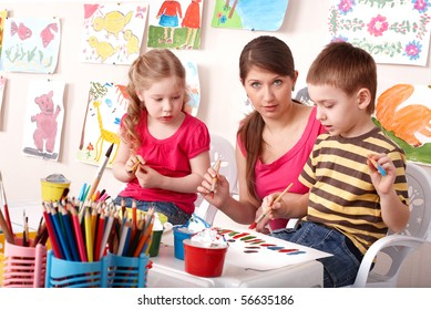 Little girl and boy  painting with teacher in school.