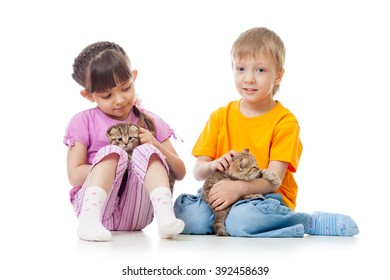 Little girl and boy playing with lovely scottish kittens isolated