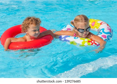 little girl and little boy playing in the pool with rubber rings