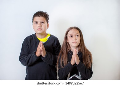 A little girl and a boy pray. Children ask for something