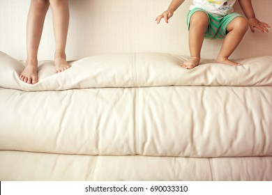 little girl and boy ready to jump from sofa to enjoy fun in house, close up of kids body