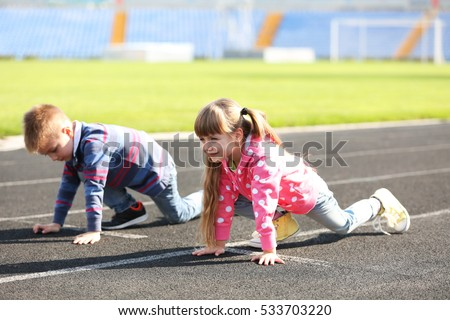 Little girl and boy in ready position to run on track