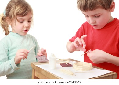 little girl and boy in red T-shirt crafts at small table, girl talking