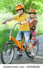 A little girl and boy riding a Bicycle in park