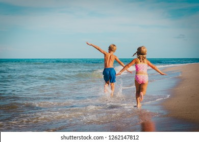 little girl and boy run fly play with waves on beach
