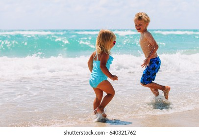 little girl and boy run play with waves on beach