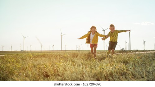Little girl and boy are running in front of windmills. Renewable energies and sustainable resources - wind mills. children playing with the wind near a wind turbine - Shutterstock ID 1827204890