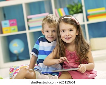 Little Girl and little boy using tablet computer at home, or in preschool. Selective focus, focus is on the girl