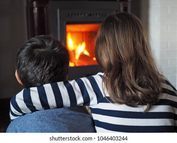 little girl and little boy warm up by the fireplace