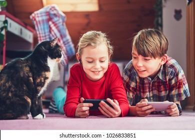 Little girl and boy watching video or playing games on their smart phones.