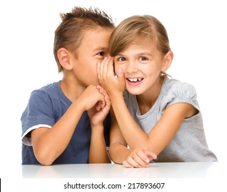 Little girl and boy are whispering in ear, isolated over white