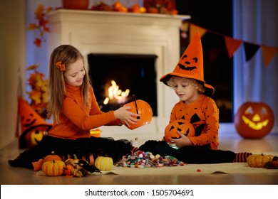 Little girl and boy in witch costume on Halloween trick or treat. Kids holding candy in pumpkin lantern bucket. Children celebrate Halloween at decorated fireplace. Family trick or treating.