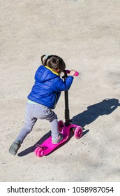 Little girl with braids and blue coat skating her pink scooter. Outdoors playful amusement for kids