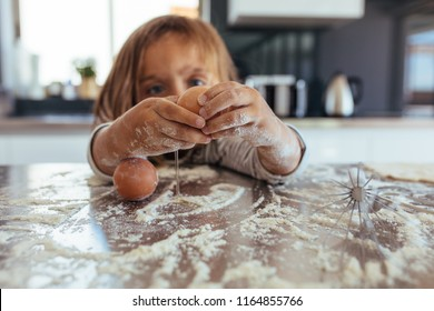 Little girl breaking an egg on kitchen counter covered with flour. Girl child learning cooking in the kitchen at home and making a mess.