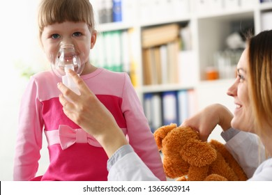 Little girl breathing with inhaler at doctor office portrait