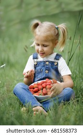 a little girl with bright red berries in the white plate on the grass in the summer in denim overalls
