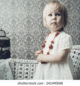Little girl with bright red jewelery posing on brick background