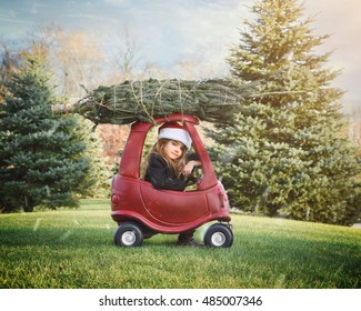 A little girl is bringing home a Christmas tree on top of a roof outside in the snow for a holiday decoration or family tradition concept.