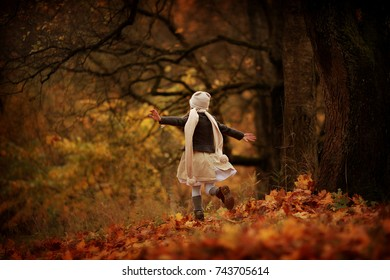 Little girl in a brown coat and a long scarf running through the autumn forest. Childhood.