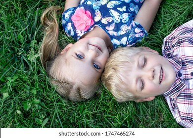A little girl with brown hair in two ponytails and a bright blue dress with butterflies and a boy in a shirt lie on the green grass and smile.