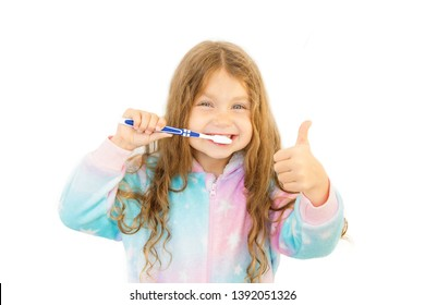 Little girl brushes her teeth and shows OK sign - thumb up. The child has wet hair after a shower and is dressed in pajamas. Teeth care and health care concept. Isolated on white background.