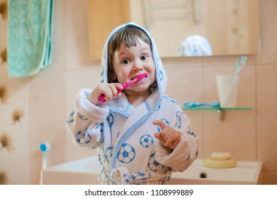 A little girl is brushing her teeth. A child in a bathrobe in the bathroom washes. Hygiene and caring for children's teeth.