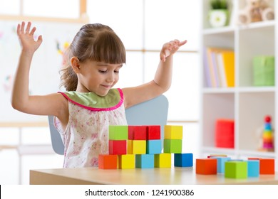 Little girl build block toys at home or daycare. Cheerful kid playing with color cubes. Educational toys for preschool and kindergarten children.