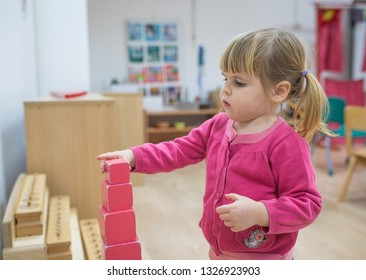 Little girl build red cube tower in Montessori classroom