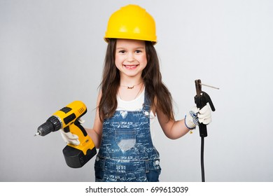 Little girl builder playing with building instrument