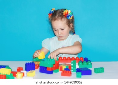 A little girl builds from a constructor. Cute child playing indoors on a blue background. Space for text