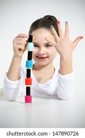 Little girl builds a pyramid using nail polishes