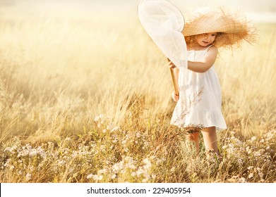 Little girl with butterfly net catching butterflies in the meadow sunny summer day