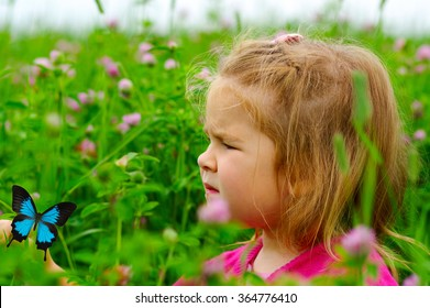 Little girl with a butterfly on field