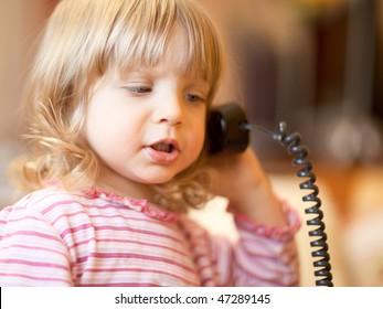 Little girl calling phone - shallow DOF, focus on front eye