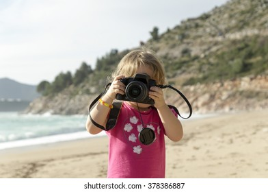 little girl with a camera on the beach