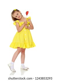 Little girl with a candy on a stick. The concept of sweets, festive mood, birthday, happiness, child, Happy childhood. Isolated over white background