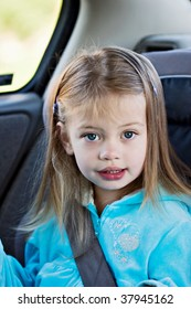 Little girl in a car seat looking at the viewer.