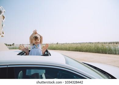 Little girl in the car waving near lake