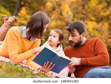 Little girl carefully listen to the fairy tale read by her parents on autumn picnic