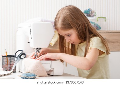 little girl carefully working with modern sewing machine