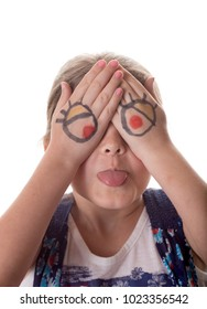 Little girl with cartoon eyes drawn on hands making goofy face.