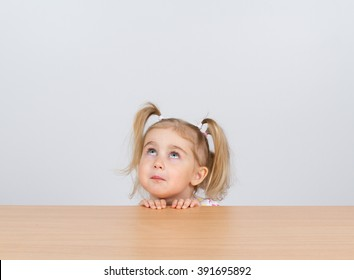 Little girl in casual clothes looking up and thinking. Sitting at the table.