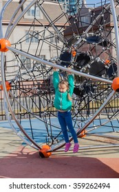 Little girl in casual clothes playing on kids playground, holding ropes and climbing. Selective focus on girls head.