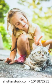 Little girl with a cat outdoors
