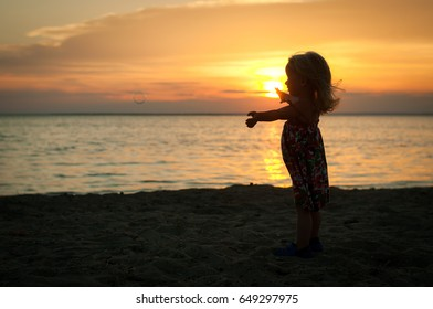 A little girl is catching soap bubbles by the sea at sunset
