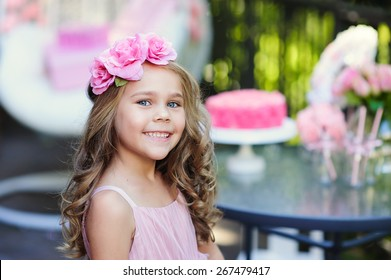 Little girl celebrate Happy Birthday Party with rose decor in the beautiful garden
