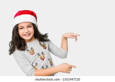 Little girl celebrating christmas day excited pointing with forefingers away.